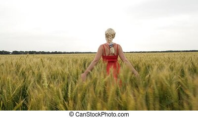 Woman with blonde hair in a red dress walking in the field...
