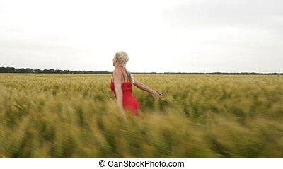 Woman with blonde hair in a red dress runs in the field with...