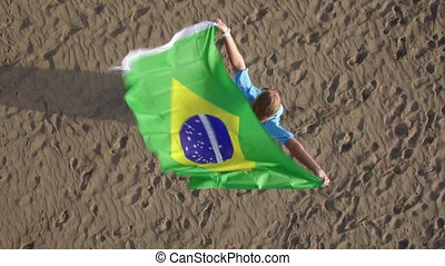 Aerial view of woman with Brazilian flag and nature scene -...