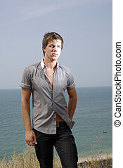 Guy in a shirt and jeans near sea