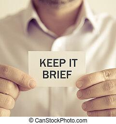 Businessman holding KEEP IT BRIEF message card - Closeup on...