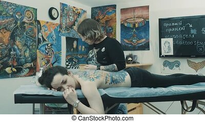 Tattooist covering tattoo with plastic film - Master...