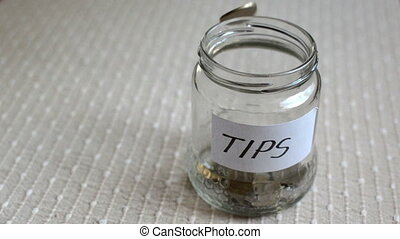 Coins filling in jar labeled for tips - Coins filling and...