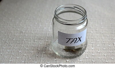 jar being filled with coins for tax