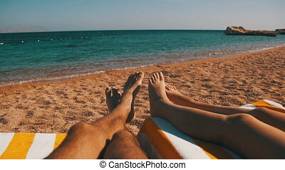Legs of Couple People Lying on Beach Sun Lounger near the...