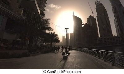 Silhouettes of buildings, trees and people walking around on the waterfront of Dubai Marina at sunset