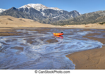 whitewater kayak in shallow water and sand dunes -...