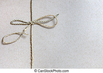 String Bow Tied over Recycled Paper with Copy Space