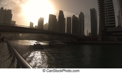 Silhouettes of two boats passing under the bridge on the waterfront of Dubai Marina at sunset