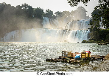 View at Detian waterfalls with bamboo raft on water in China