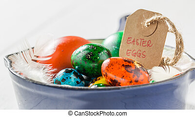 Colourfull Easter eggs with feathers in pan
