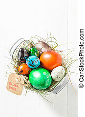 Colourfull Easter eggs in the bucket with hay