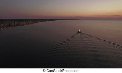 Aerial shot of sailing boat and distant coast at night -...