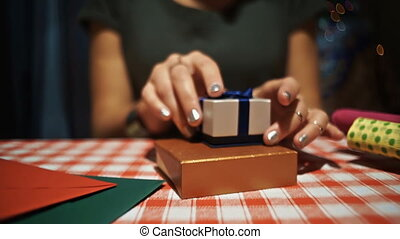 Female opening a small blue secret present box with a silver ring inside it
