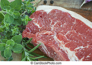 Raw Beef Steak with Fresh Herbs on Board