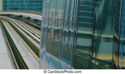 The subway train rides among the glass skyscrapers in Dubai,...