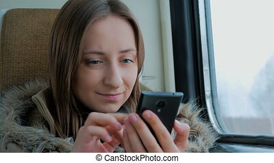 Pensive woman traveling on a train and using a smartphone -...