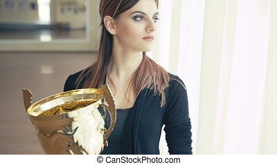 Portrait of pretty girl with golden glowing trophy cup...