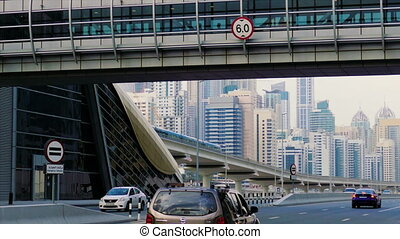 a futuristic urban landscape with a pedestrian crossing going over the highway in Dubai, United Arab Emirates