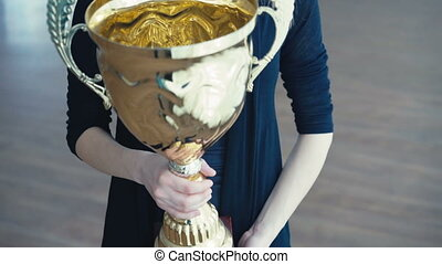 Portrait of pretty girl with golden glowing trophy cup