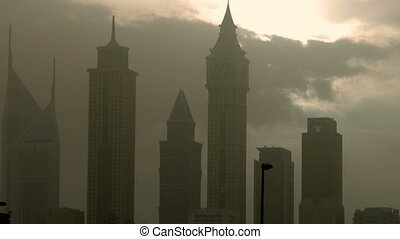 urban landscape, with large skyscrapers and the sun breaking...