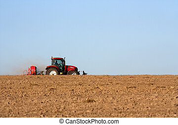 Tractor with plough - Big tractor ploughing a field
