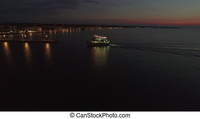 Flying over touristic ship finishing night sea tour - Aerial...