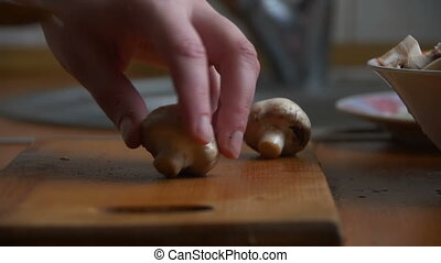 Slicing mushrooms on a kitchen board - Female cook cuts...