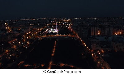 Aerial view of night Valencia with fun fair in park - Flying...