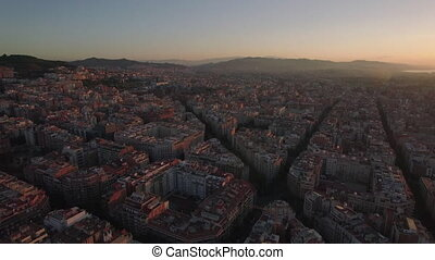 Aerial cityscape of Barcelona at sunset - Flying over...