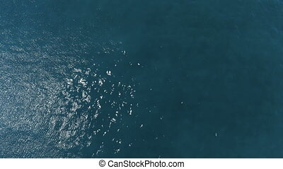 Slow motion fly over disturbed ocean water surface made in...
