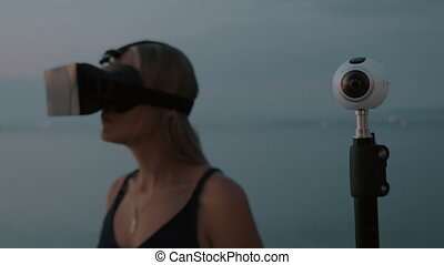 360 degree camera and woman with VR glasses - Shot with...