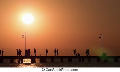 Timelapse of people traffic on the pier at sunset -...