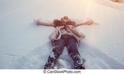 Happy young woman in winter lying in snowdrift in slow...