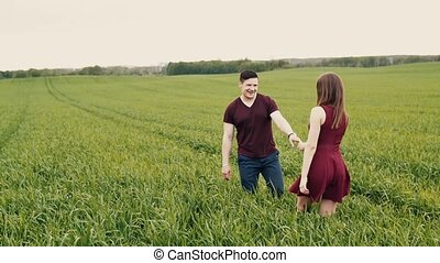 Young couple walk in forest through the lilac bushes. Lovers...