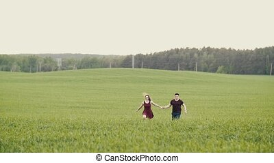 A couple in love running through a wheat field, holding...