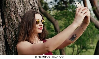 beautiful young woman with long dark hair in sunglasses taking selfie, at the park at sunset. slow mo