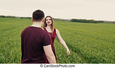 Romantic young couple. They hug and spin around in a green...