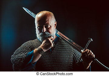 Powerful bearded knight with the sword on the dark...