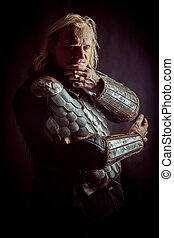 Powerful blond knight is standing with the crossed arms on the dark background
