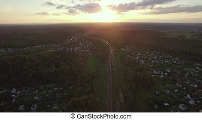 Flying over countryside and freight train at sunset, Russia