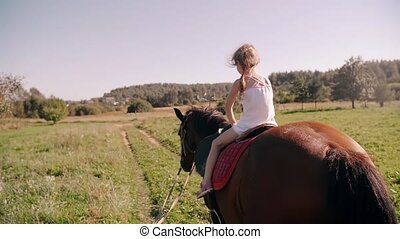 A happy little girl riding a horse in the nature on a sunny...