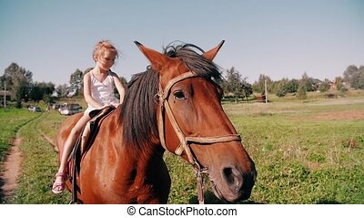 A happy little girl riding a horse on a country road on a...
