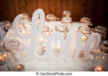 The word LOVE on white cloth around burning candles. Handmade. Scenery