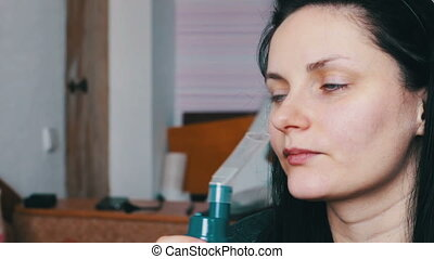 Woman uses a nebuliser for asthma and lung disease at home -...