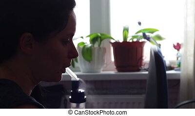 The girl inhales medicine for asthma through the nebulizer -...