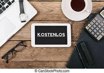 German Kostenlos (Free of charge) on screen of table computer at office desk