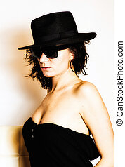 Girl with smudged make up and hat on head and glasses
