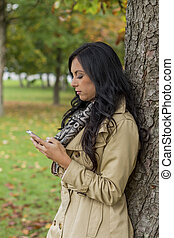 woman writes sms - a young woman writes on his mobile phone...