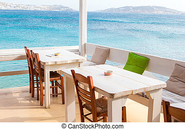 Summer empty openair cafe with sea view - White tables with...